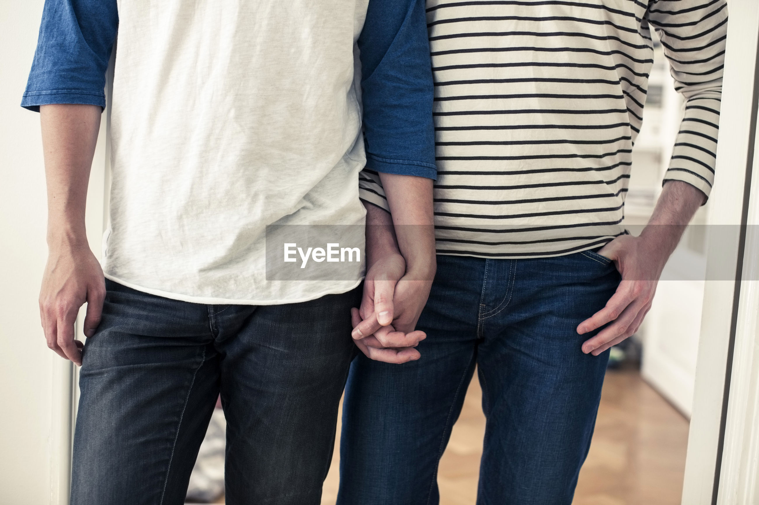 MIDSECTION OF COUPLE STANDING AGAINST BLUE WALL