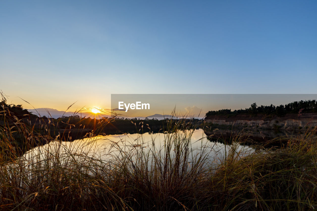 sky, tranquility, scenics - nature, beauty in nature, tranquil scene, sunset, water, plant, nature, no people, mountain, non-urban scene, grass, environment, copy space, landscape, clear sky, lake, idyllic, outdoors