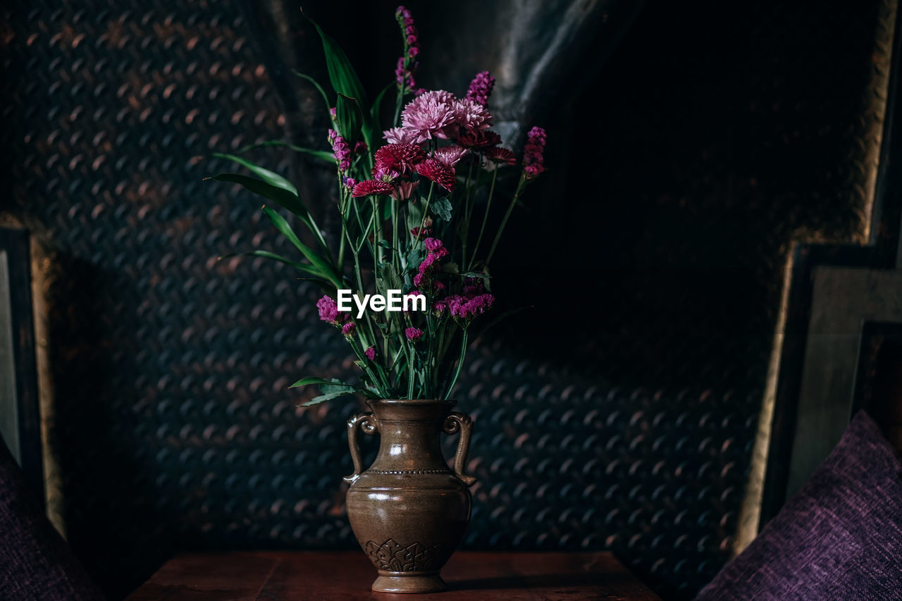 flowering plant, plant, flower, table, vase, freshness, indoors, no people, potted plant, fragility, nature, beauty in nature, vulnerability, close-up, focus on foreground, seat, pink color, flower head, chair, plant part, flower pot, flower arrangement, purple, place mat