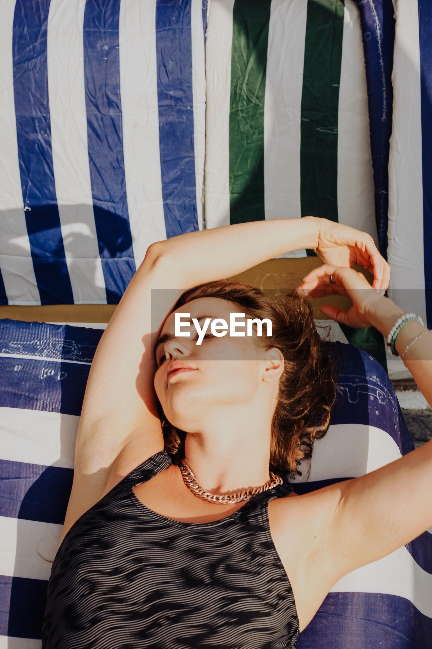 HIGH ANGLE VIEW OF YOUNG WOMAN LYING ON FLOOR