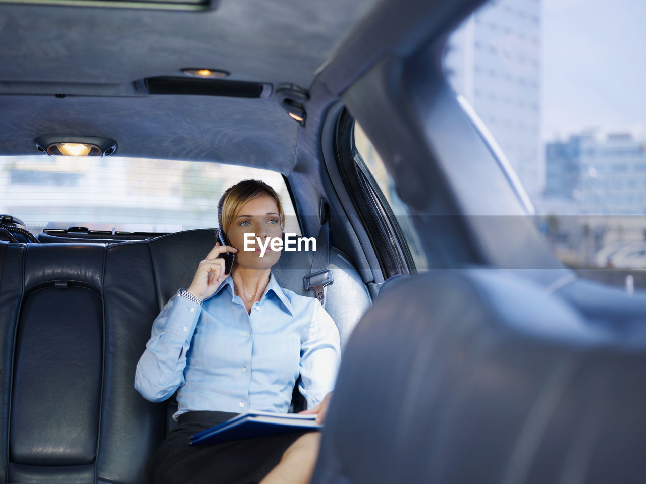 Businesswoman talking on phone while sitting in car