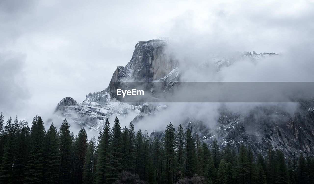 Scenic view of snowcapped mountains in foggy weather