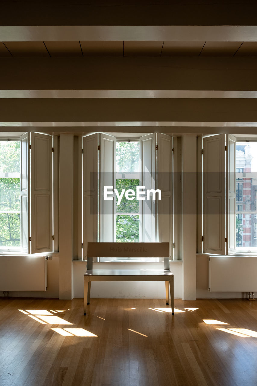 window, indoors, home interior, architecture, day, glass - material, no people, flooring, built structure, sunlight, empty, hardwood floor, building, house, wood - material, nature, wood, tree, domestic room, ceiling