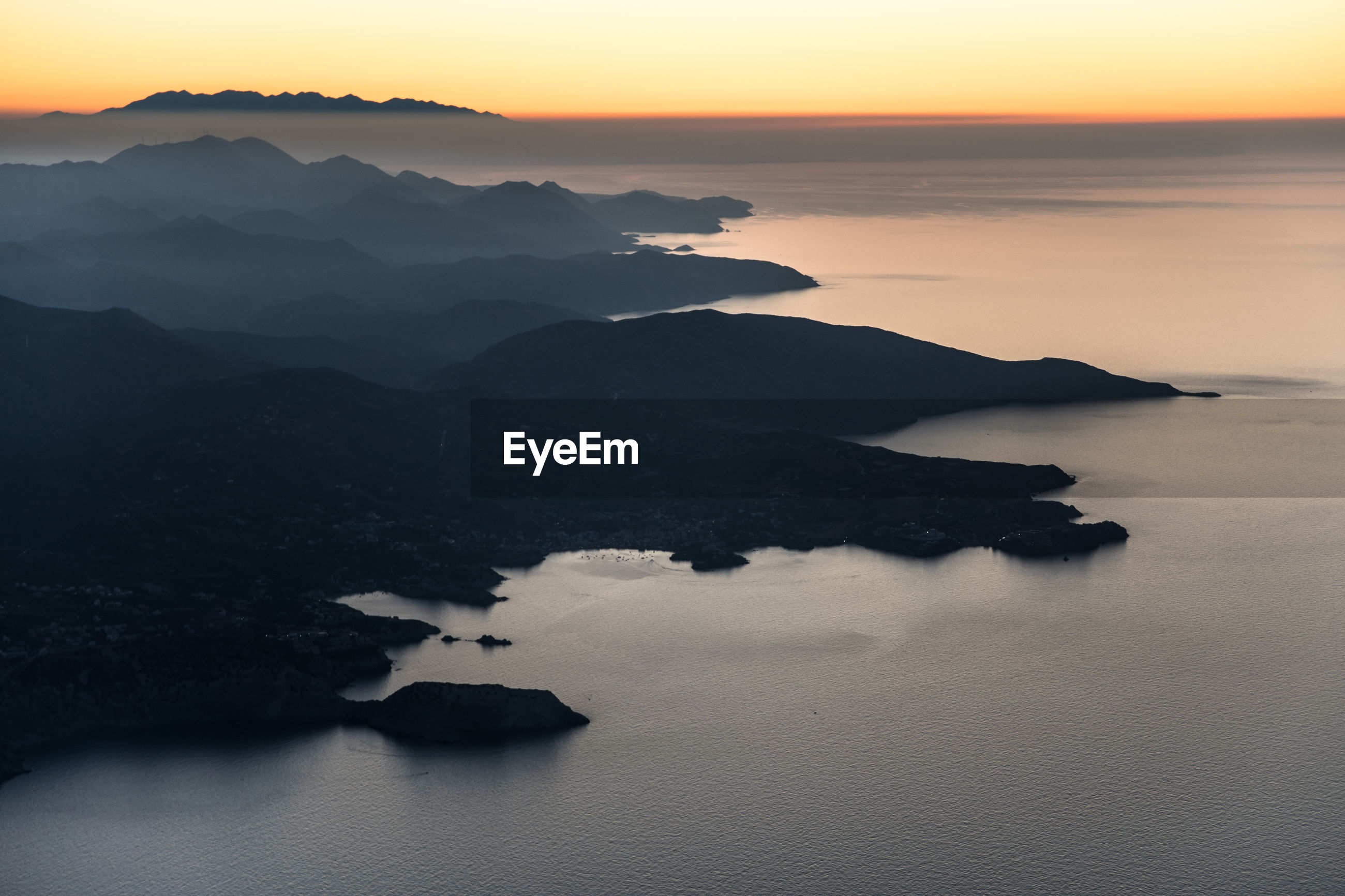 SCENIC VIEW OF SEA BY SILHOUETTE MOUNTAIN AGAINST SKY DURING SUNSET