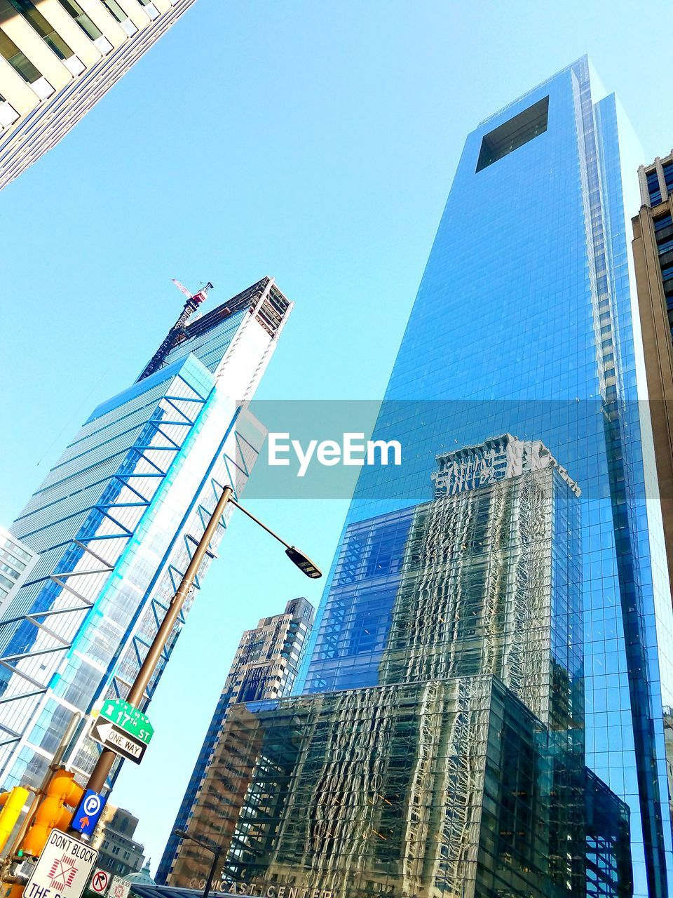 skyscraper, architecture, building exterior, built structure, city, low angle view, tall - high, modern, tower, office building, tall, financial district, day, downtown district, blue, development, clear sky, outdoors, city life, travel destinations, growth, no people, cityscape, urban skyline, corporate business, office park, sky