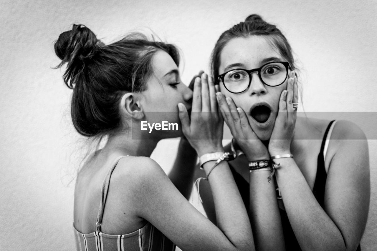 Girl whispering in friends ear against wall