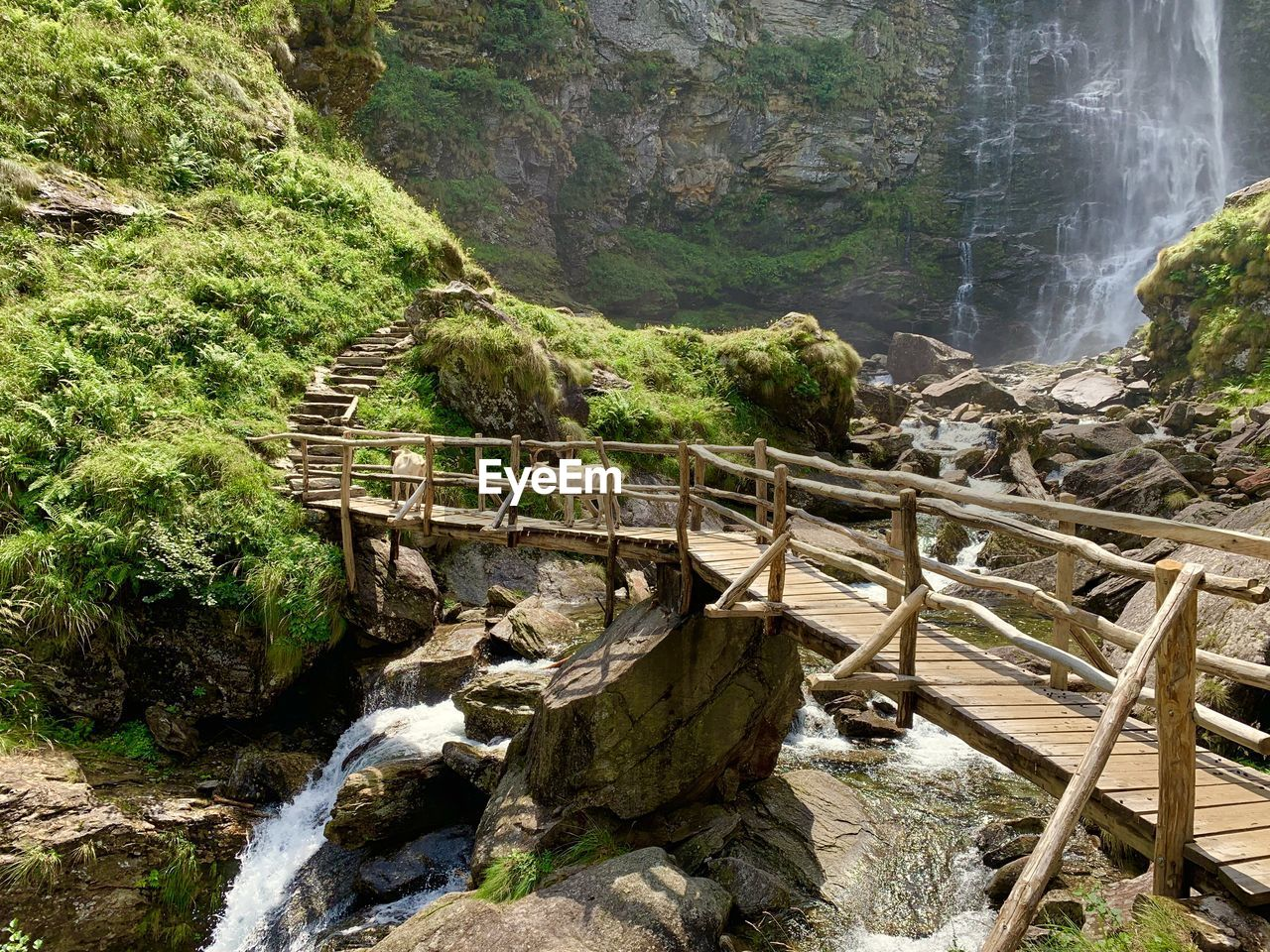 water, scenics - nature, rock, beauty in nature, solid, rock - object, nature, motion, waterfall, land, day, tree, flowing water, tranquility, no people, plant, wood - material, non-urban scene, tranquil scene, outdoors, flowing, footbridge, stream - flowing water