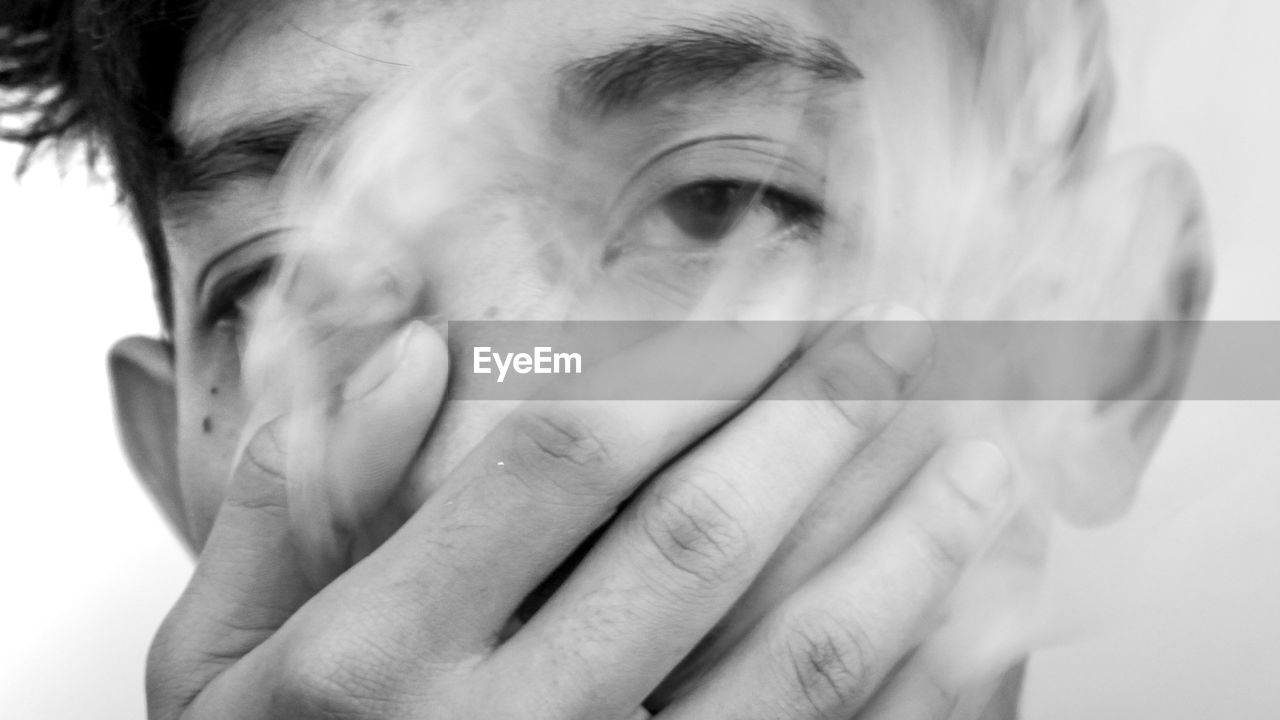 Close-up portrait of boy breathing out smoke against white background