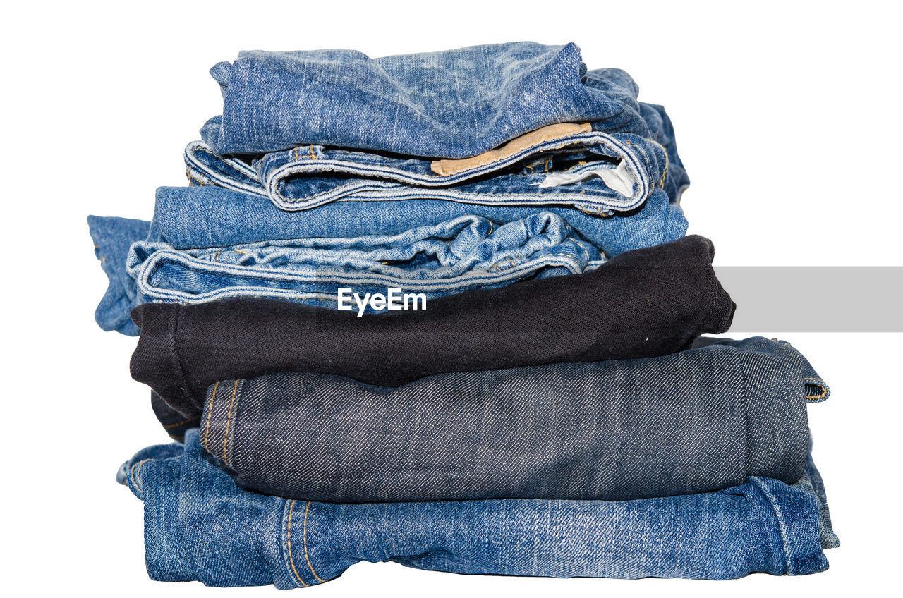 Close up-of jeans stacked against white background