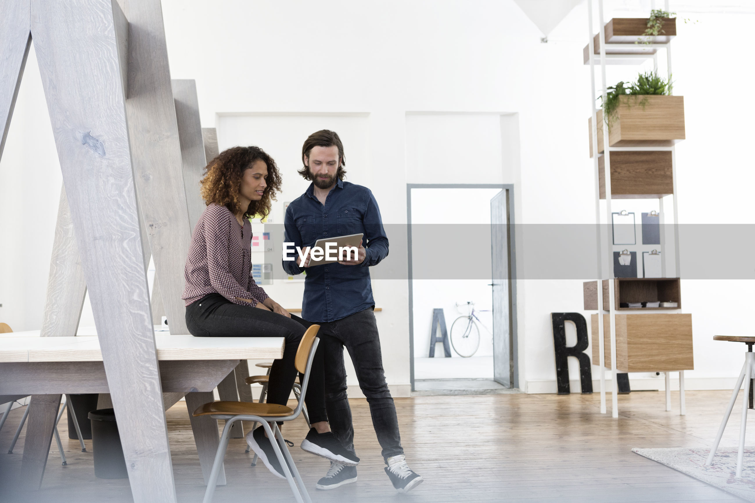 FULL LENGTH OF YOUNG COUPLE SITTING ON TABLE