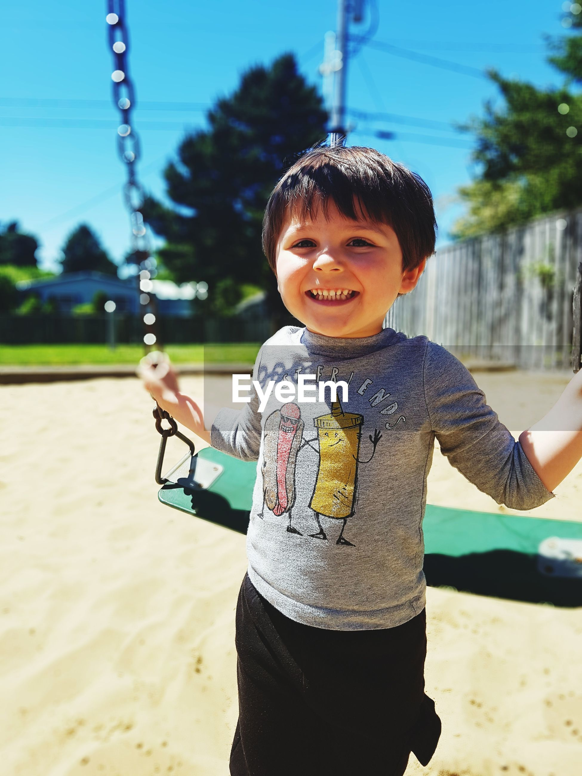 Portrait of happy boy holding swing at playground