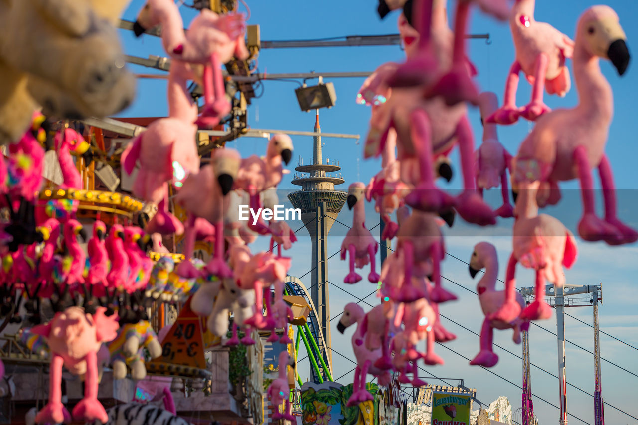 representation, selective focus, large group of objects, day, creativity, focus on foreground, art and craft, pink color, no people, human representation, hanging, nature, close-up, sky, for sale, outdoors, arrangement, choice, toy