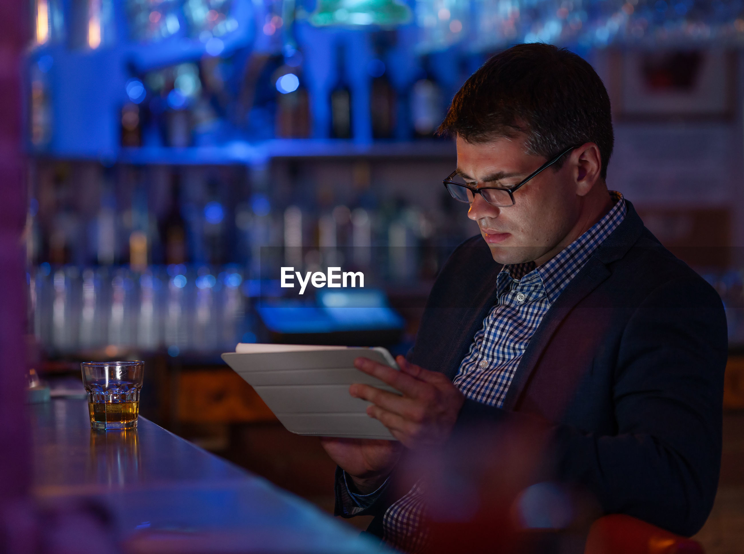 Businessman using digital tablet at bar