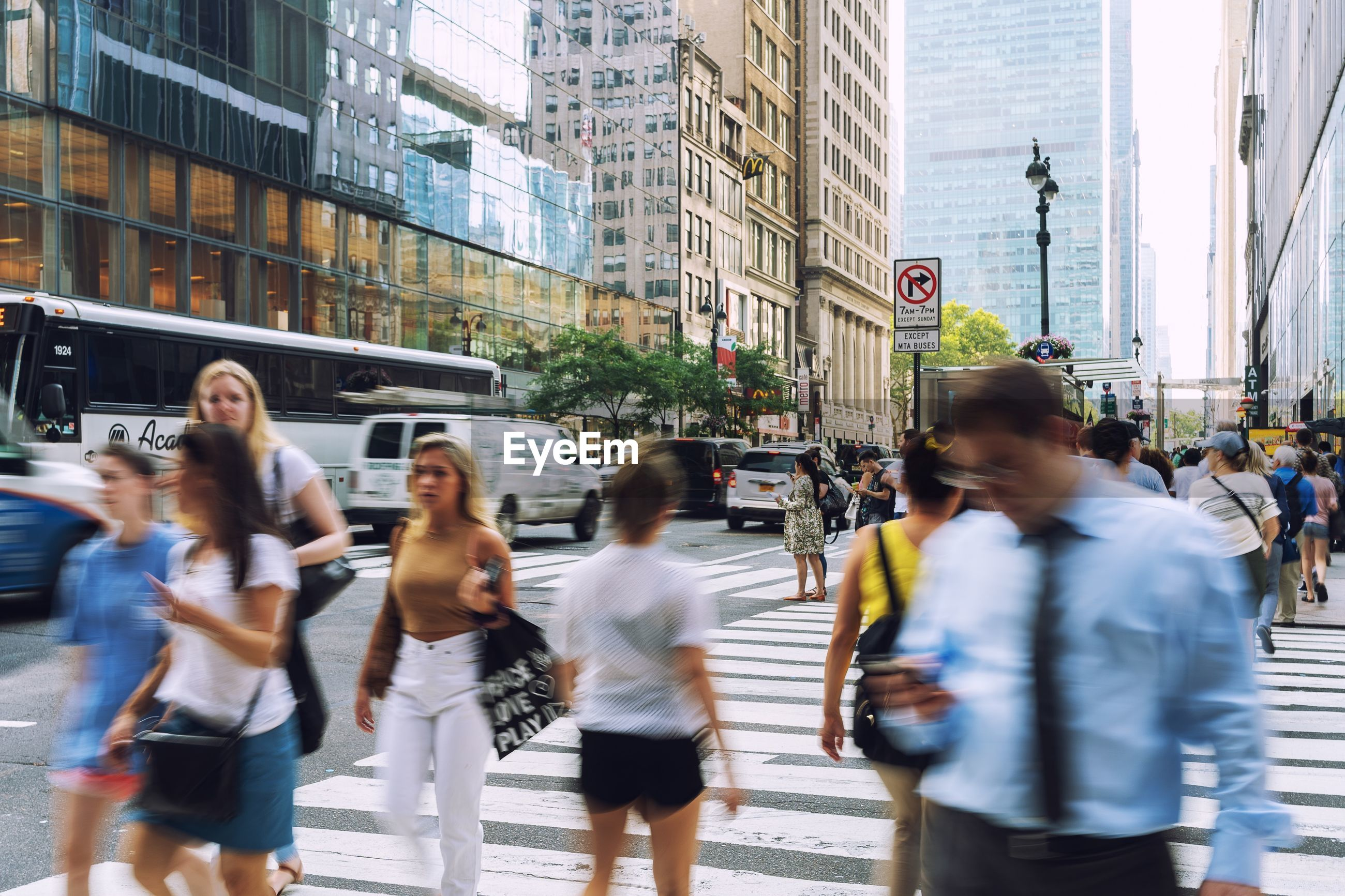 Blurred motion of people crossing road in city