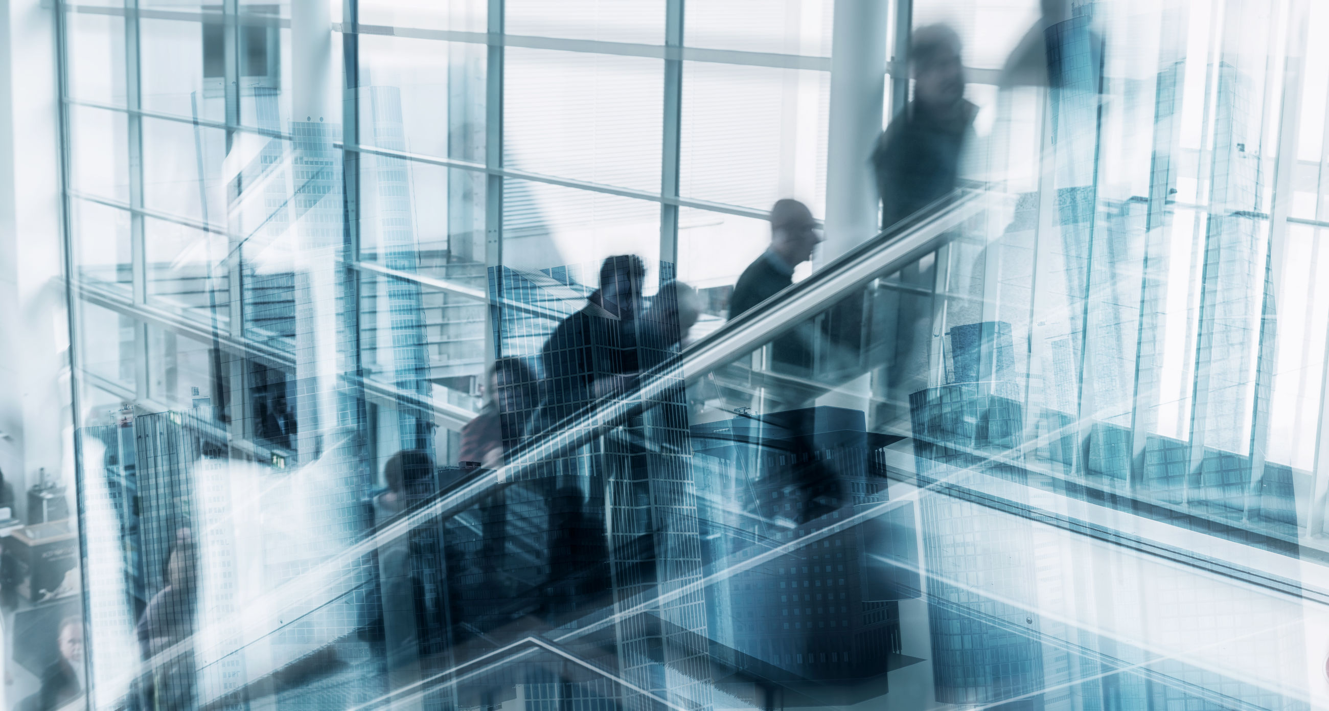 Business people standing on escalator seen through glass window