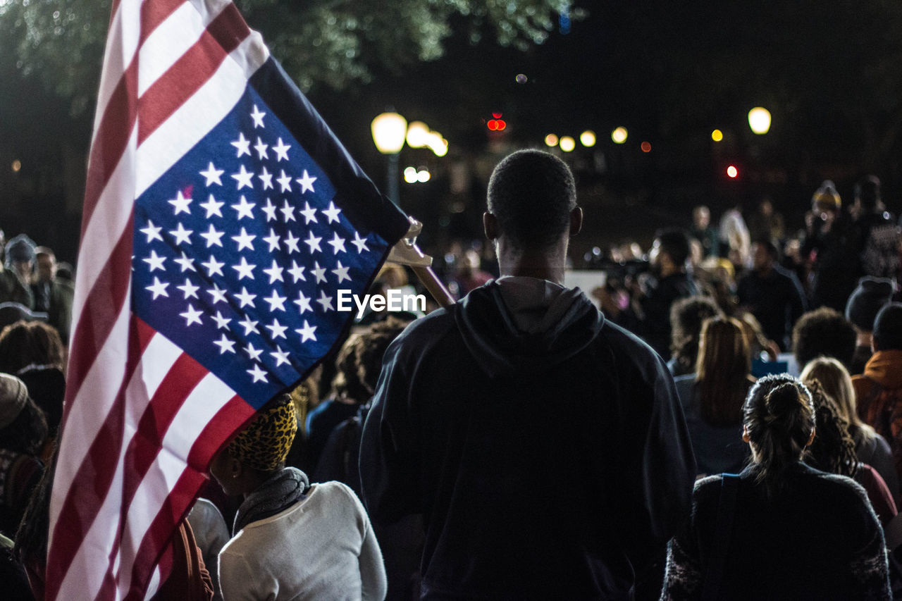 Rear View Of Man Holding American Flag In Crowd
