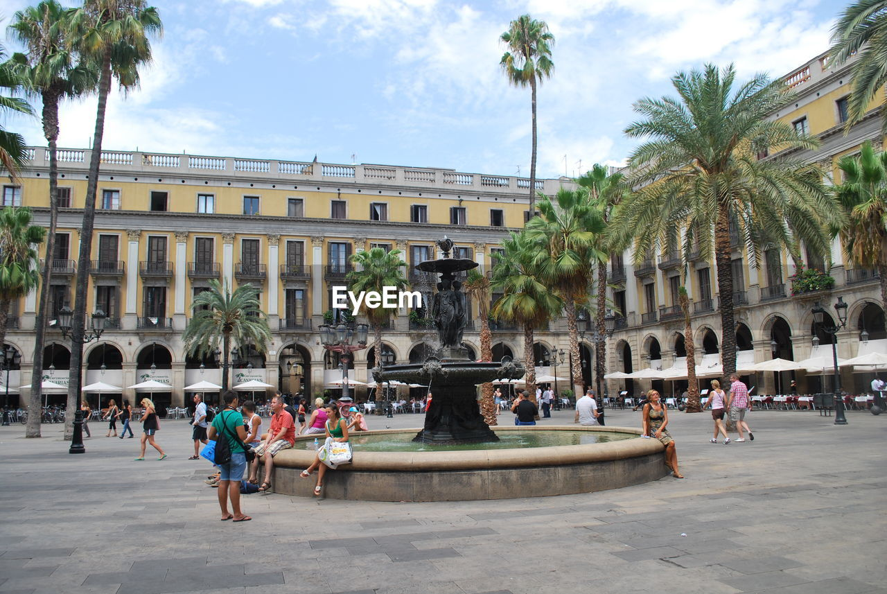 architecture, fountain, large group of people, built structure, palm tree, building exterior, real people, travel destinations, tourism, history, sky, architectural column, tree, statue, travel, outdoors, water, leisure activity, lifestyles, day, women, sculpture, men, vacations, people