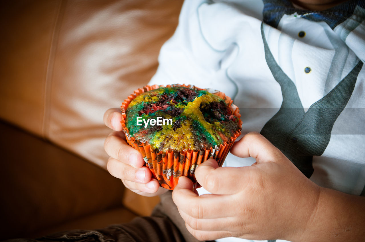 Midsection Of Boy Holding Cupcake At Home
