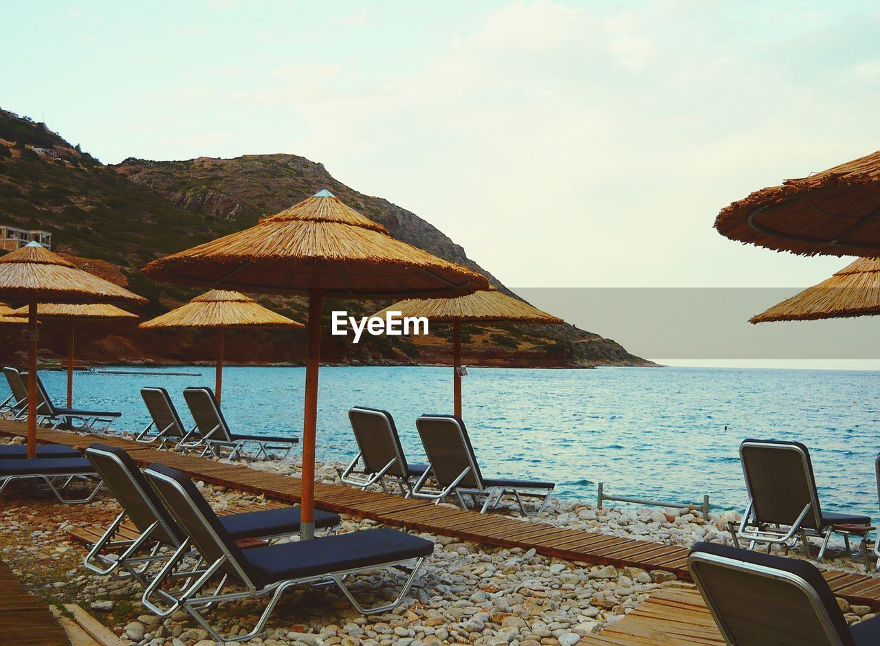 water, sky, chair, sea, land, beach, seat, nature, tranquility, scenics - nature, beauty in nature, lounge chair, tranquil scene, day, parasol, mountain, no people, cloud - sky, deck chair, outdoors