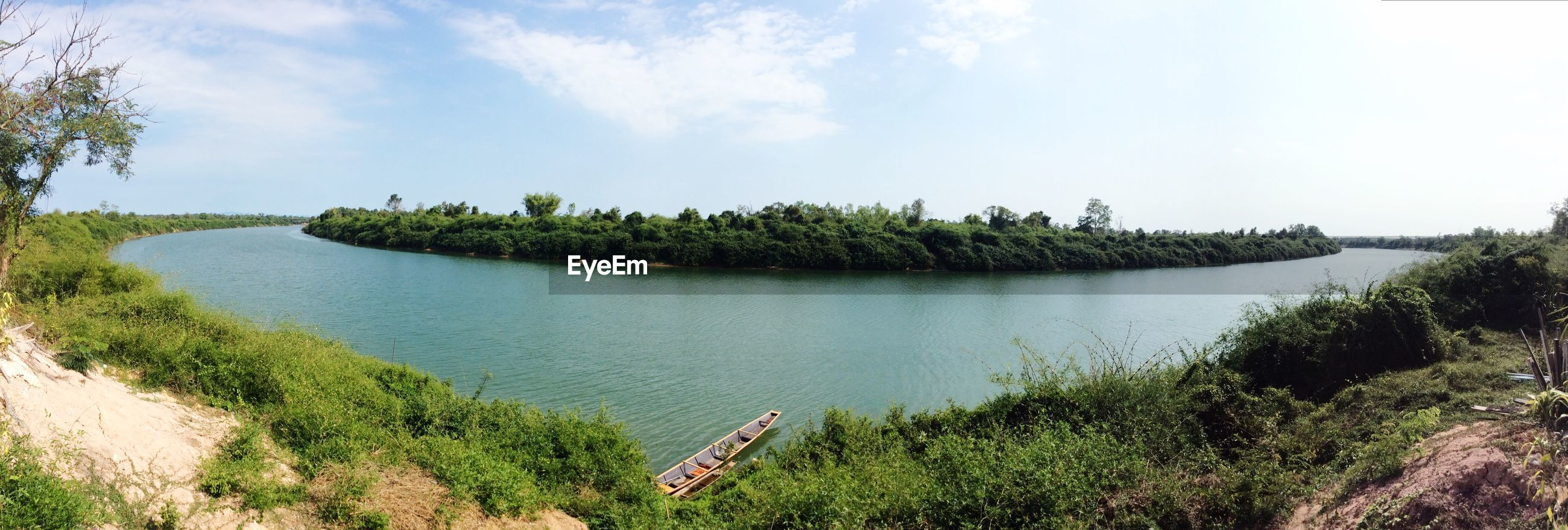 Panoramic view of river amidst field against sky