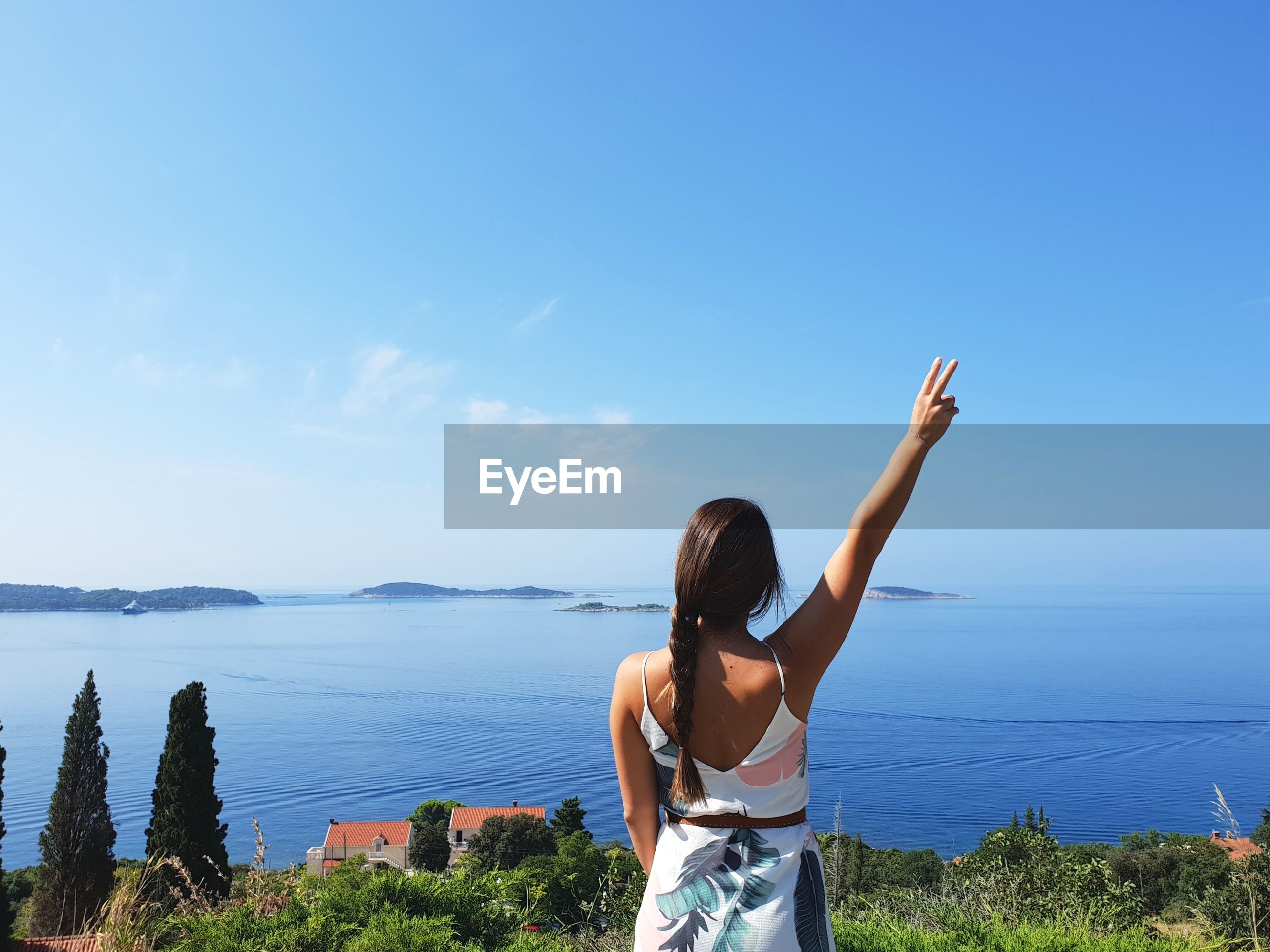 Rear view of woman with hand raised standing by sea against blue sky during sunny day