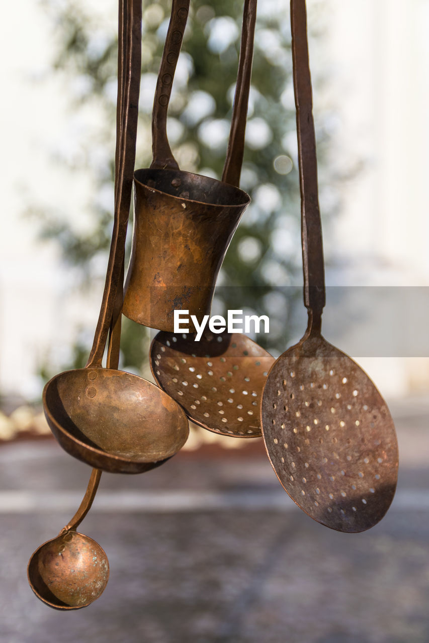 metal, focus on foreground, no people, close-up, hanging, kitchen utensil, rusty, still life, pattern, day, household equipment, old, ladle, outdoors, cooking utensil, selective focus, wall - building feature, nature, antique, steel
