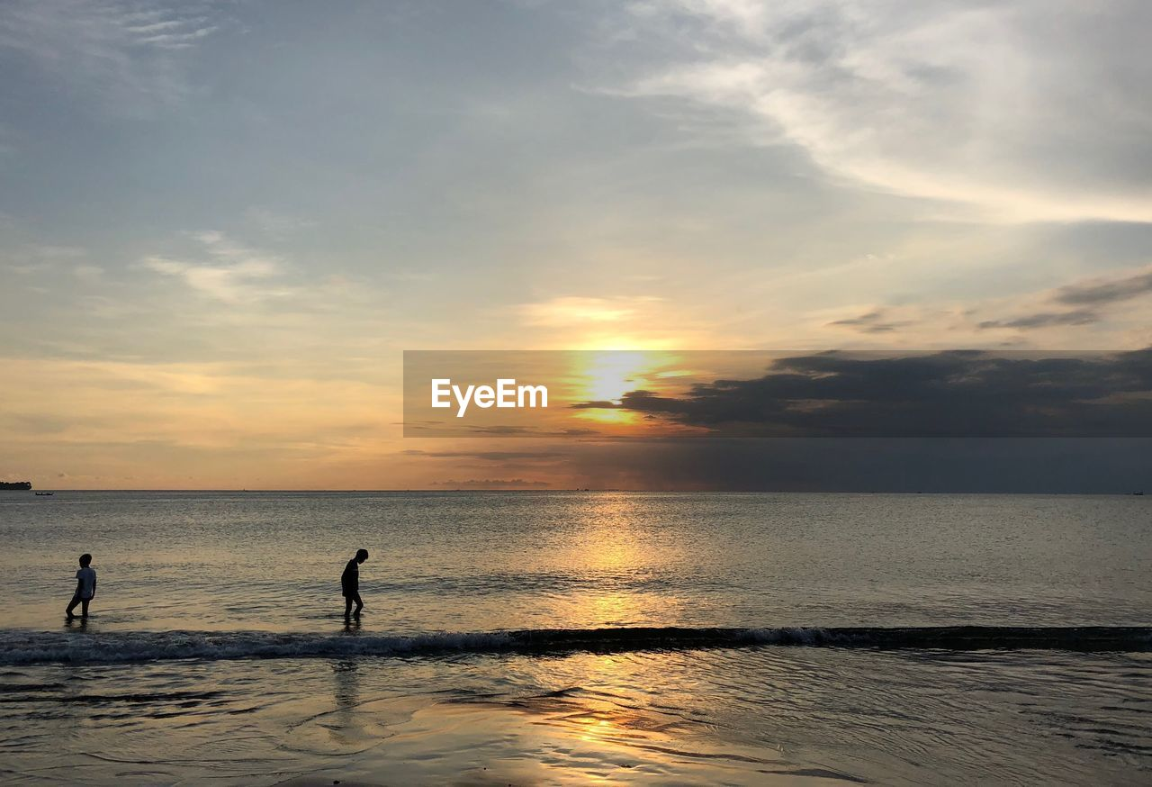 sky, sea, water, sunset, horizon over water, horizon, cloud - sky, scenics - nature, beauty in nature, beach, real people, land, leisure activity, silhouette, nature, men, lifestyles, two people, tranquility, outdoors