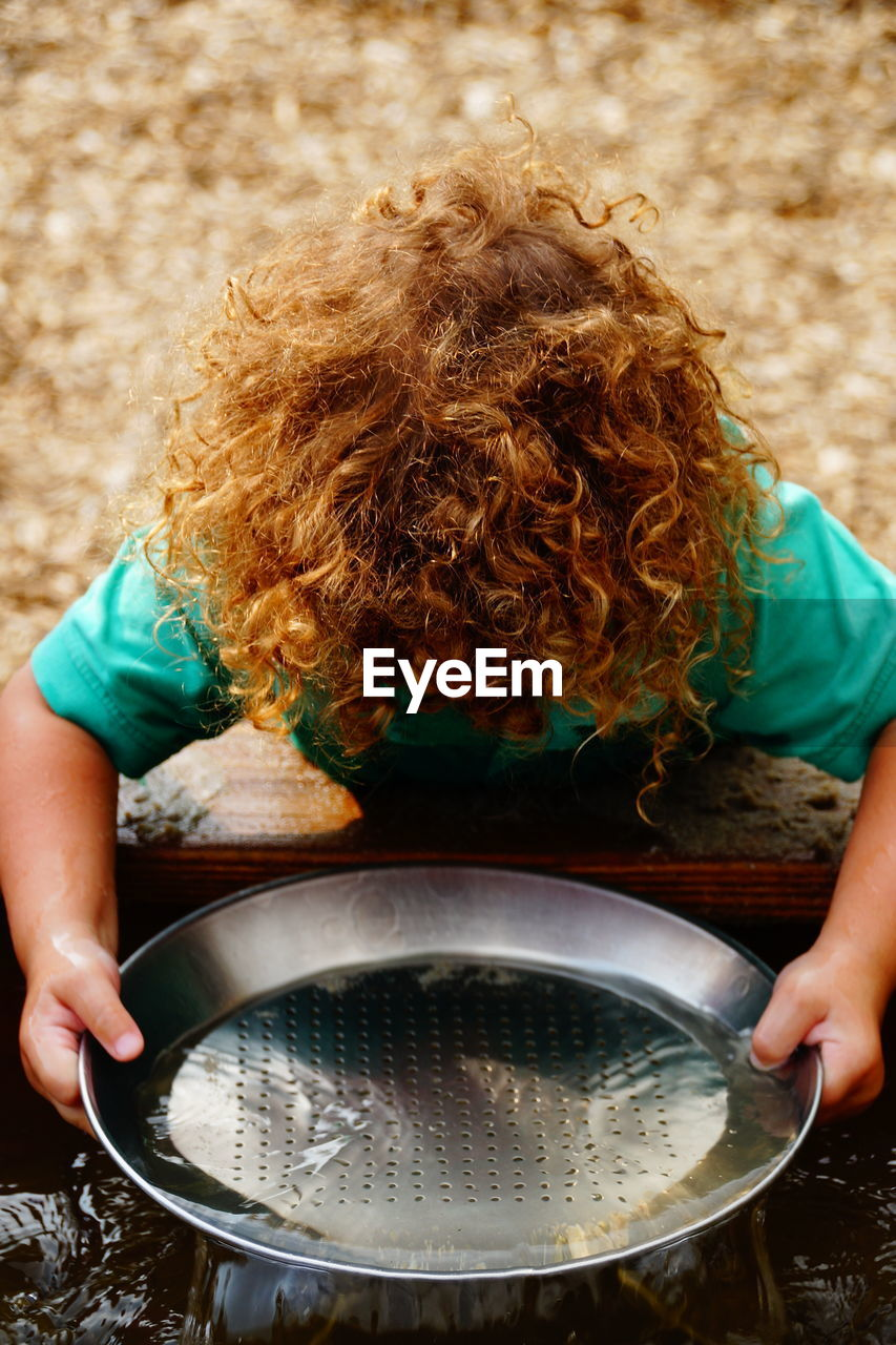 High Angle View Of Boy With Blond Curly Hair Washing Plate In Trough
