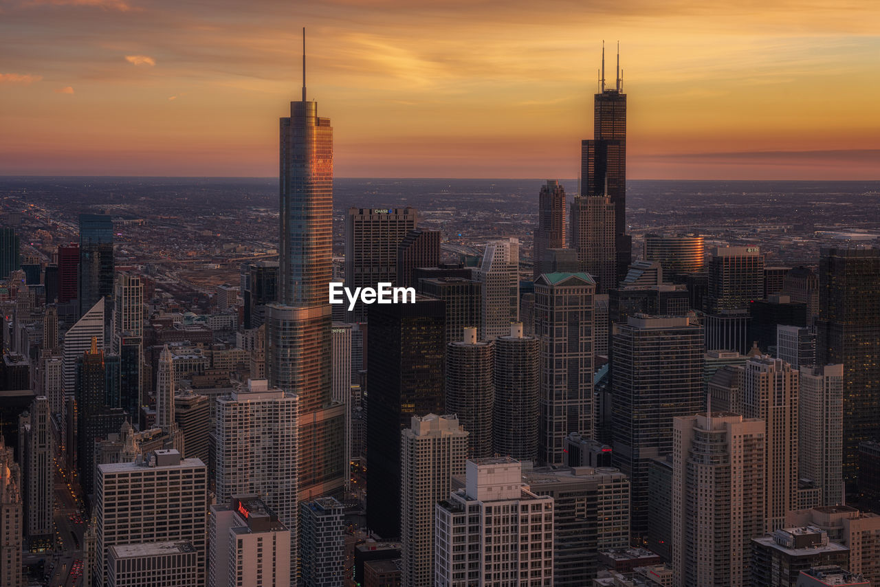 building exterior, sunset, built structure, architecture, sky, building, city, office building exterior, skyscraper, tall - high, cityscape, tower, modern, downtown district, travel destinations, residential district, office, no people, orange color, urban skyline, outdoors, financial district, spire
