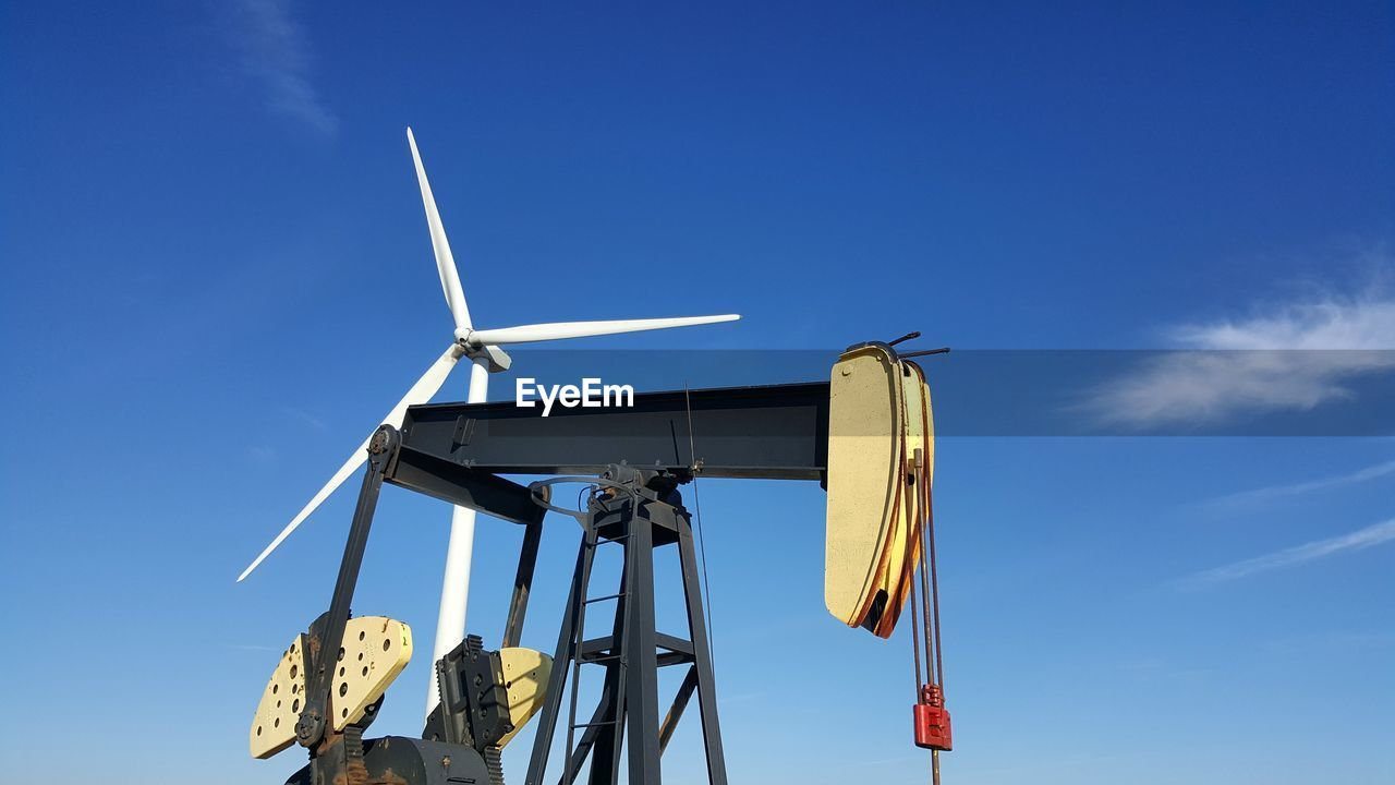 Low Angle View Of Oil Drill And Wind Turbine Against Blue Sky