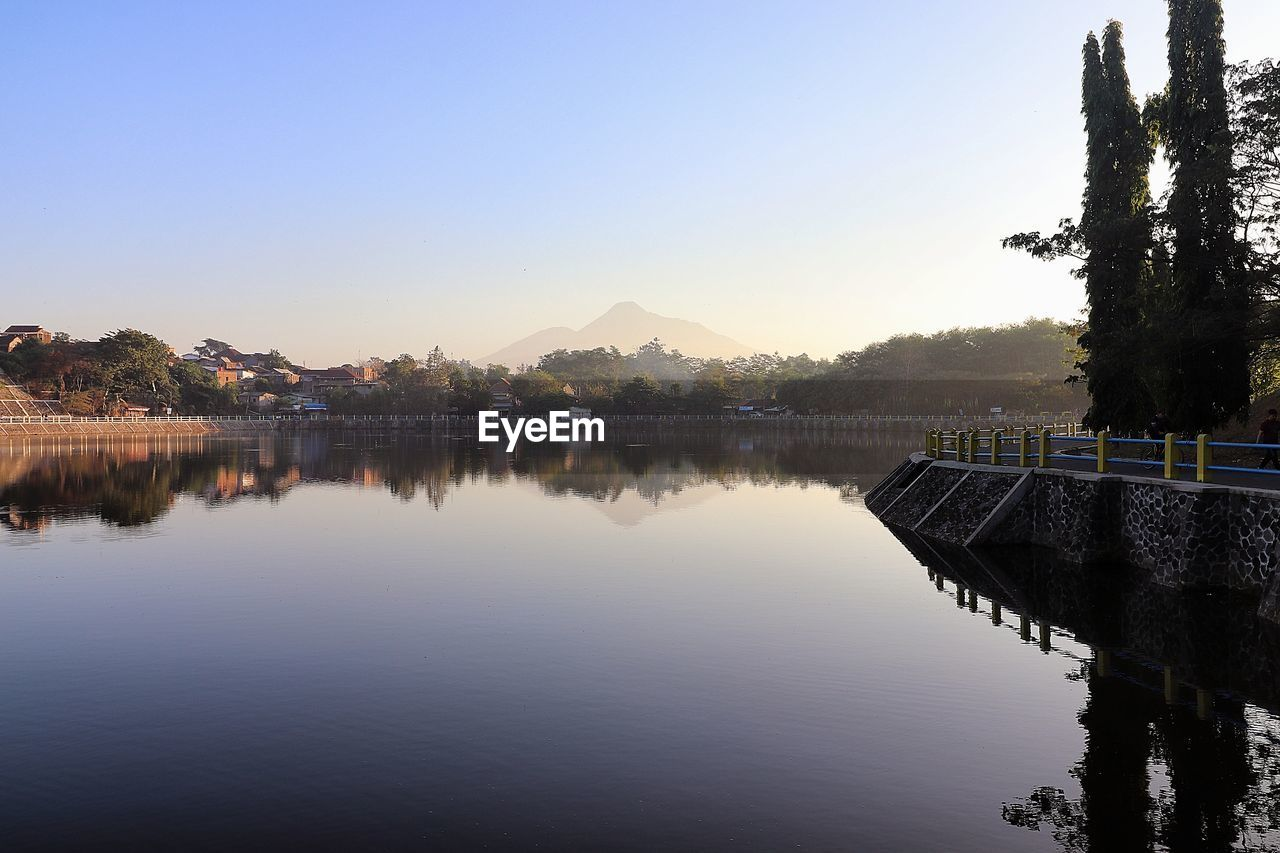 water, sky, reflection, tree, lake, waterfront, tranquility, nature, beauty in nature, scenics - nature, no people, plant, tranquil scene, architecture, copy space, clear sky, built structure, non-urban scene, outdoors