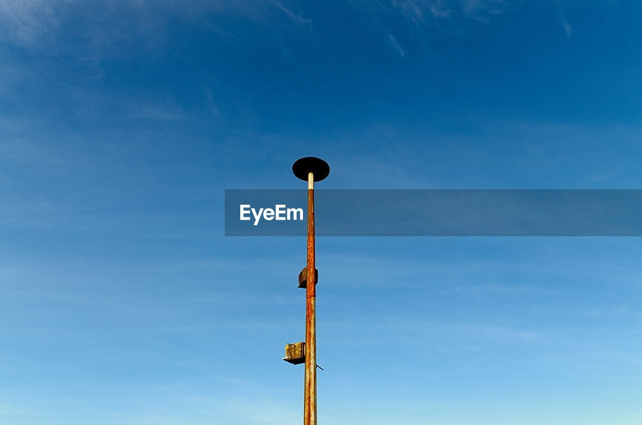 sky, low angle view, day, lighting equipment, blue, nature, cloud - sky, no people, street, pole, street light, outdoors, tall - high, technology, architecture, built structure, electricity, sunlight, tranquility, metal