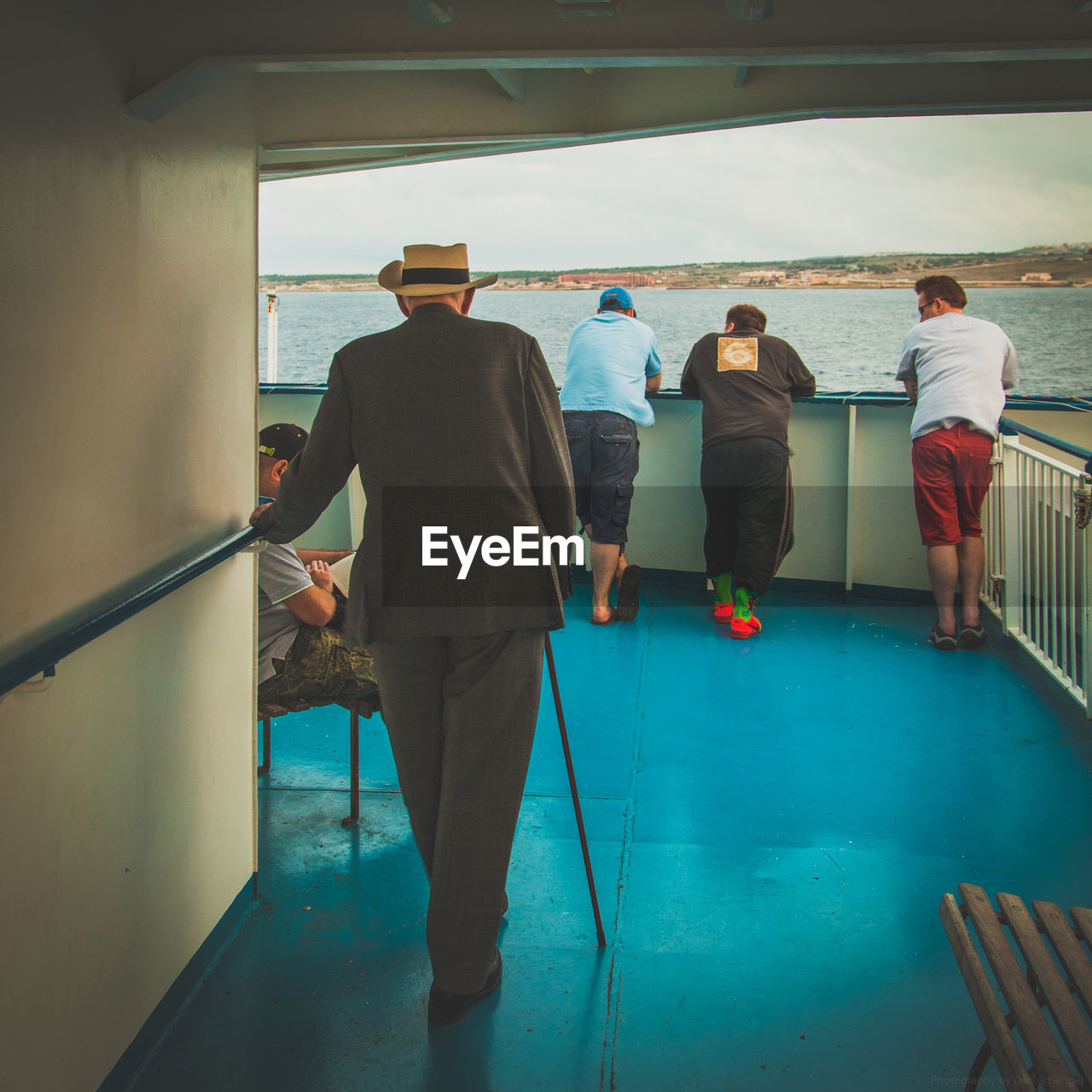 Rear view of people standing on ship