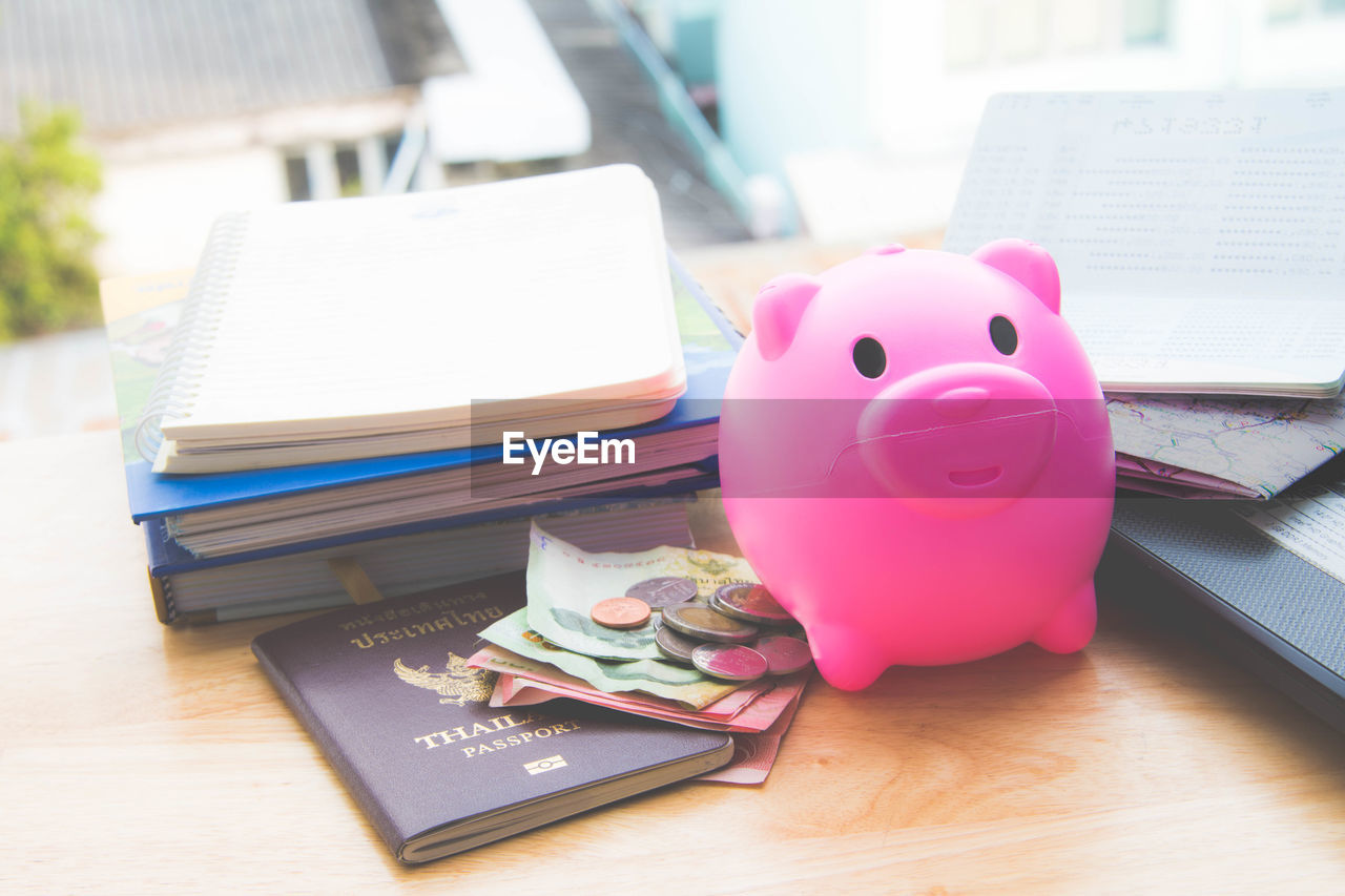 High angle view of money with piggybank and passport by books on table