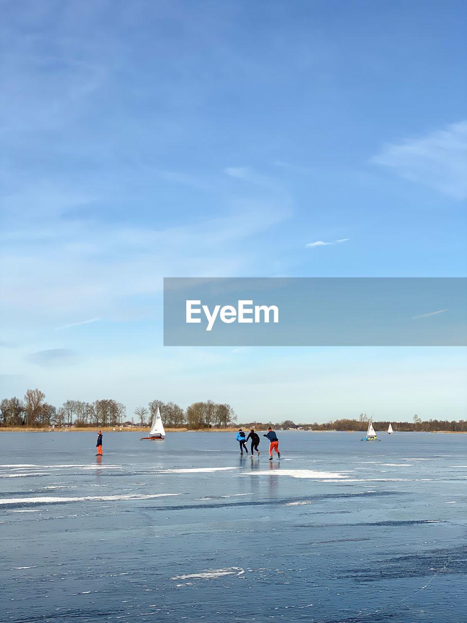 PEOPLE WALKING ON FROZEN LAKE AGAINST SKY