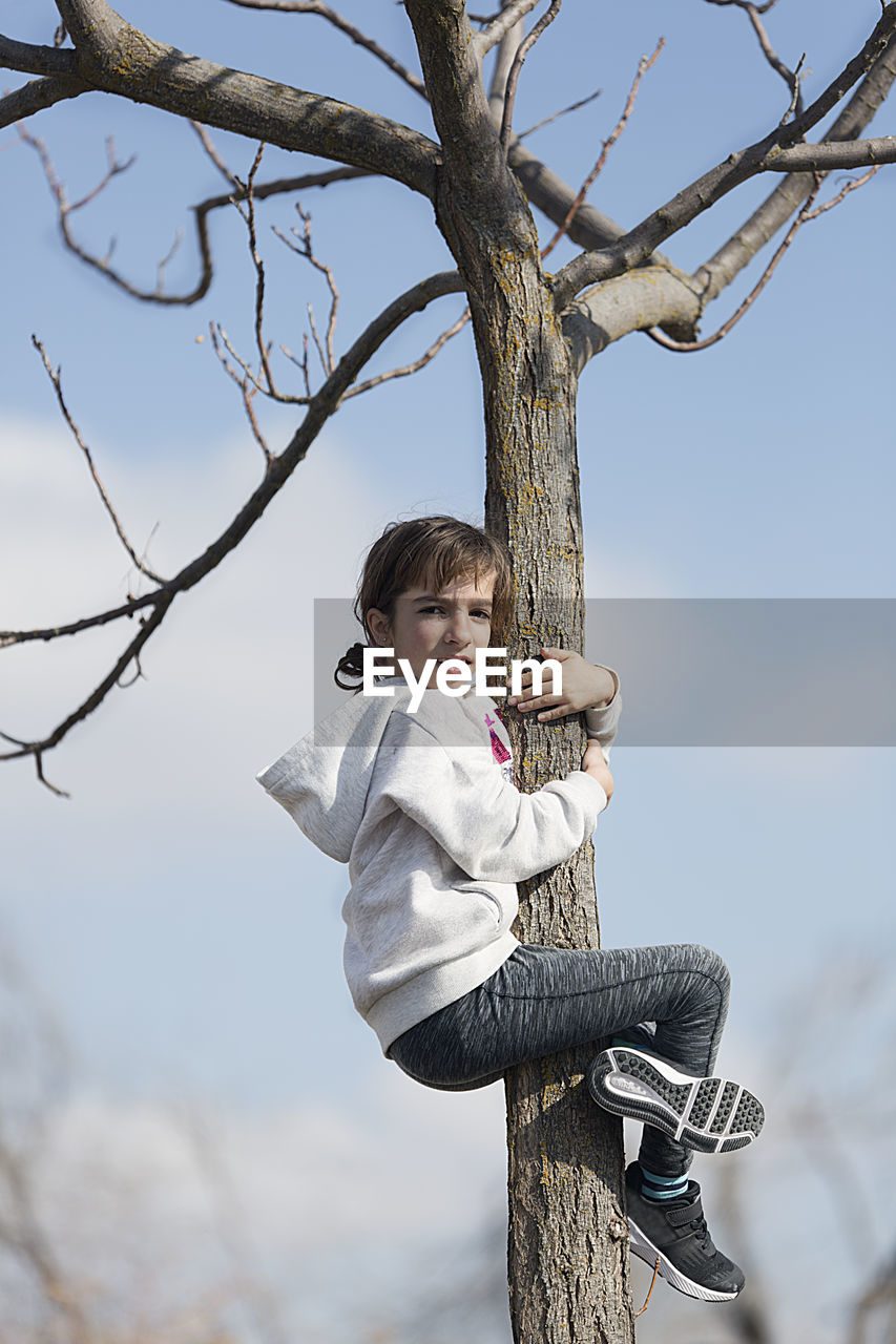 Side View Portrait Of Girl Climbing Tree Against Sky