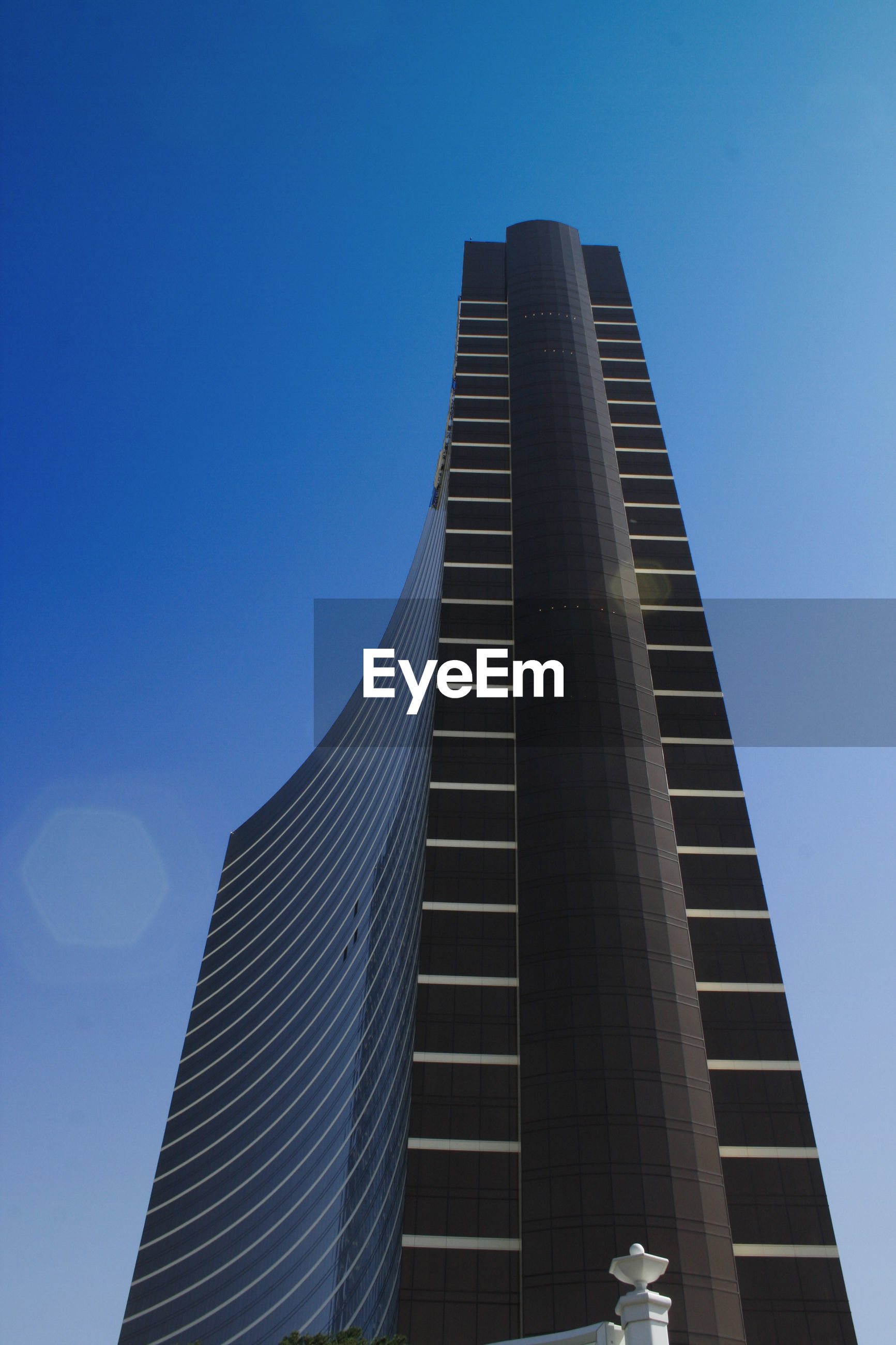 low angle view, architecture, built structure, building exterior, clear sky, blue, modern, tall - high, skyscraper, city, office building, tower, building, copy space, tall, day, outdoors, capital cities, sunlight, city life