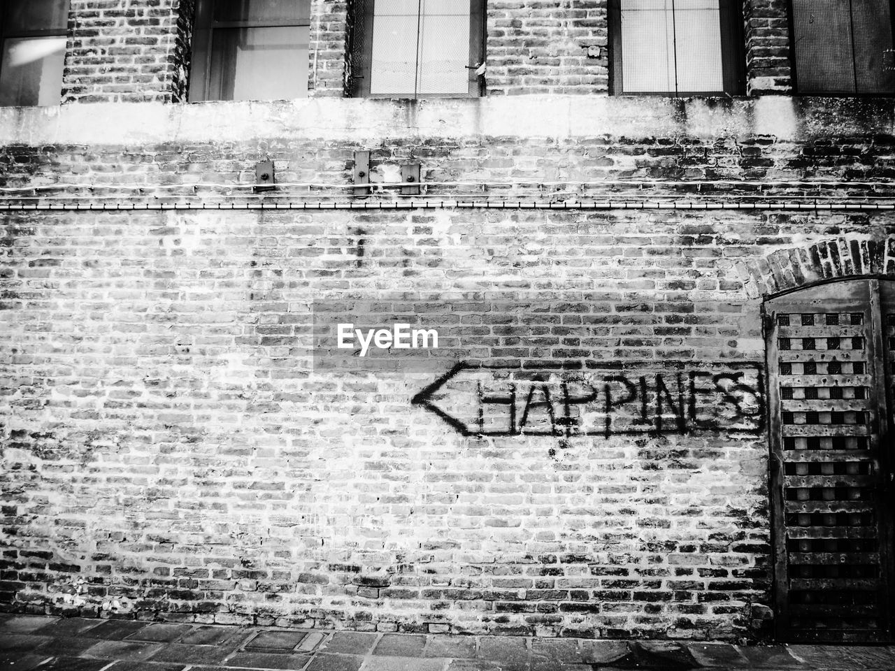Arrow symbol with happiness text on brick wall
