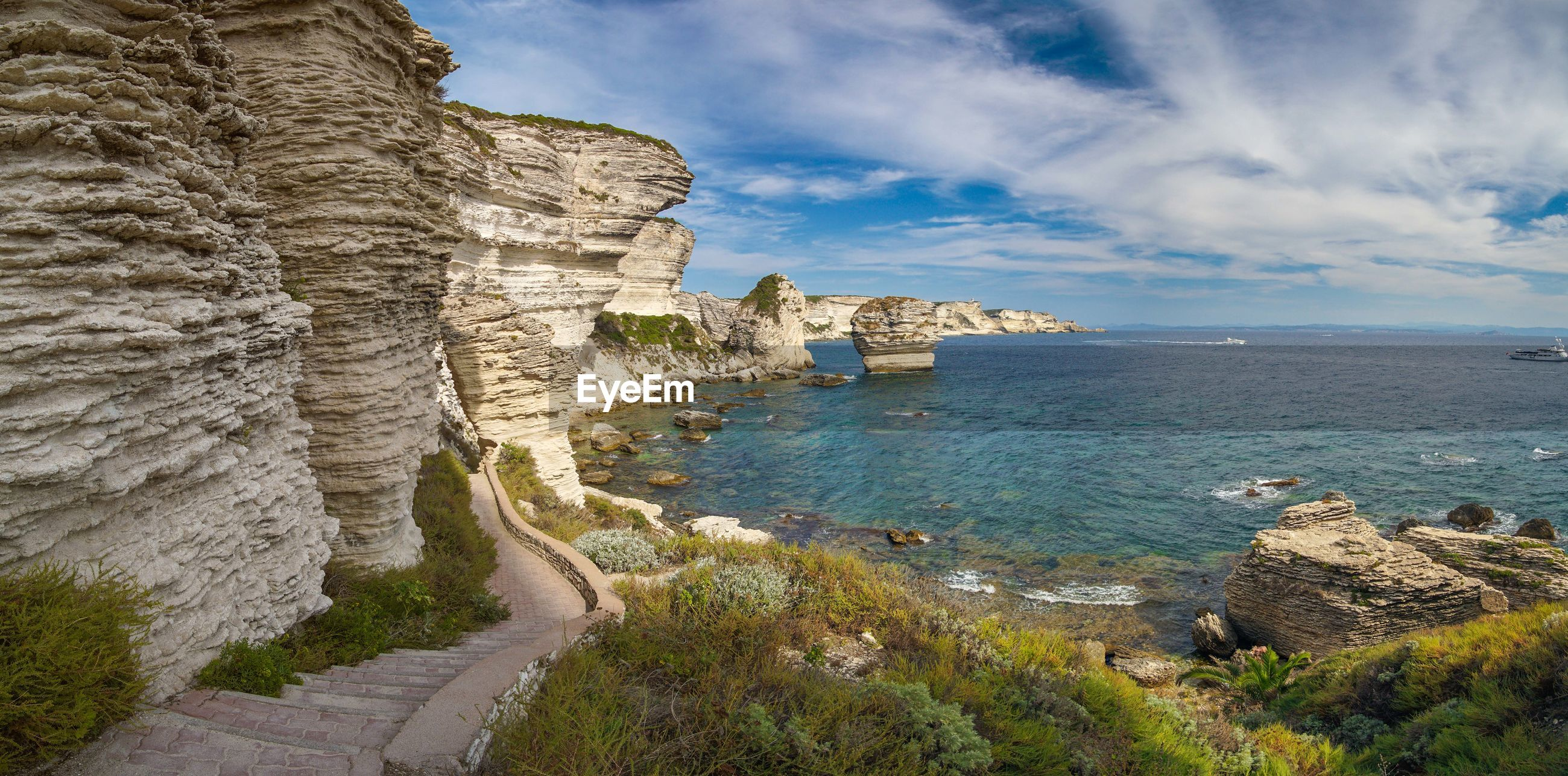 Scenic view of rock formation by sea against sky