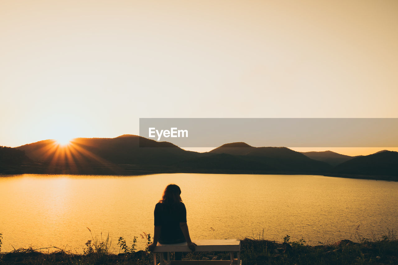 Rear View Of Woman Sitting By Lake Against Sky During Sunset