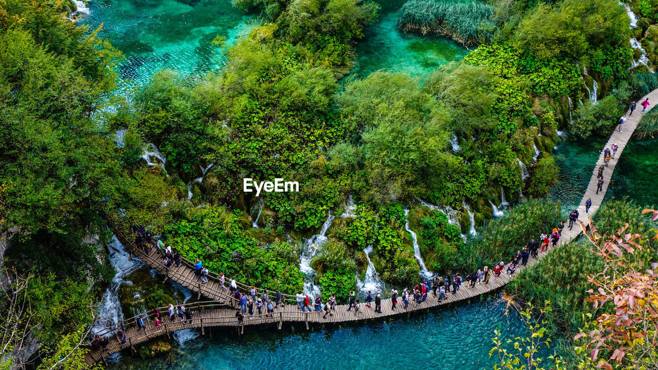 HIGH ANGLE VIEW OF PEOPLE BY BOATS IN RIVER