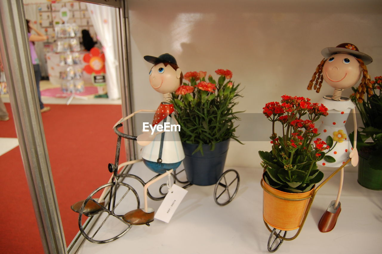representation, indoors, human representation, art and craft, no people, decoration, creativity, plant, still life, potted plant, toy, table, flower, nature, female likeness, craft, close-up, home interior, red
