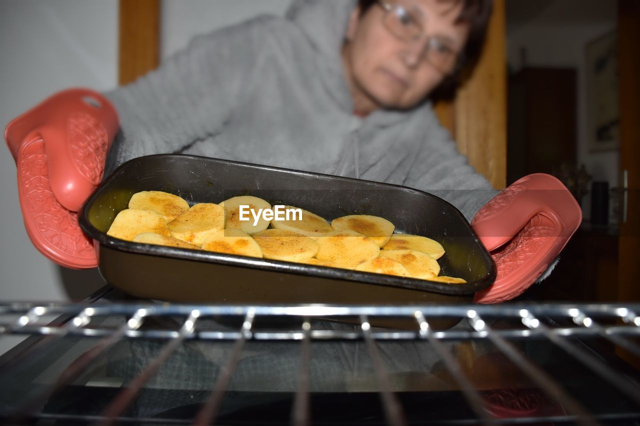 Woman holding food by metal grate in oven