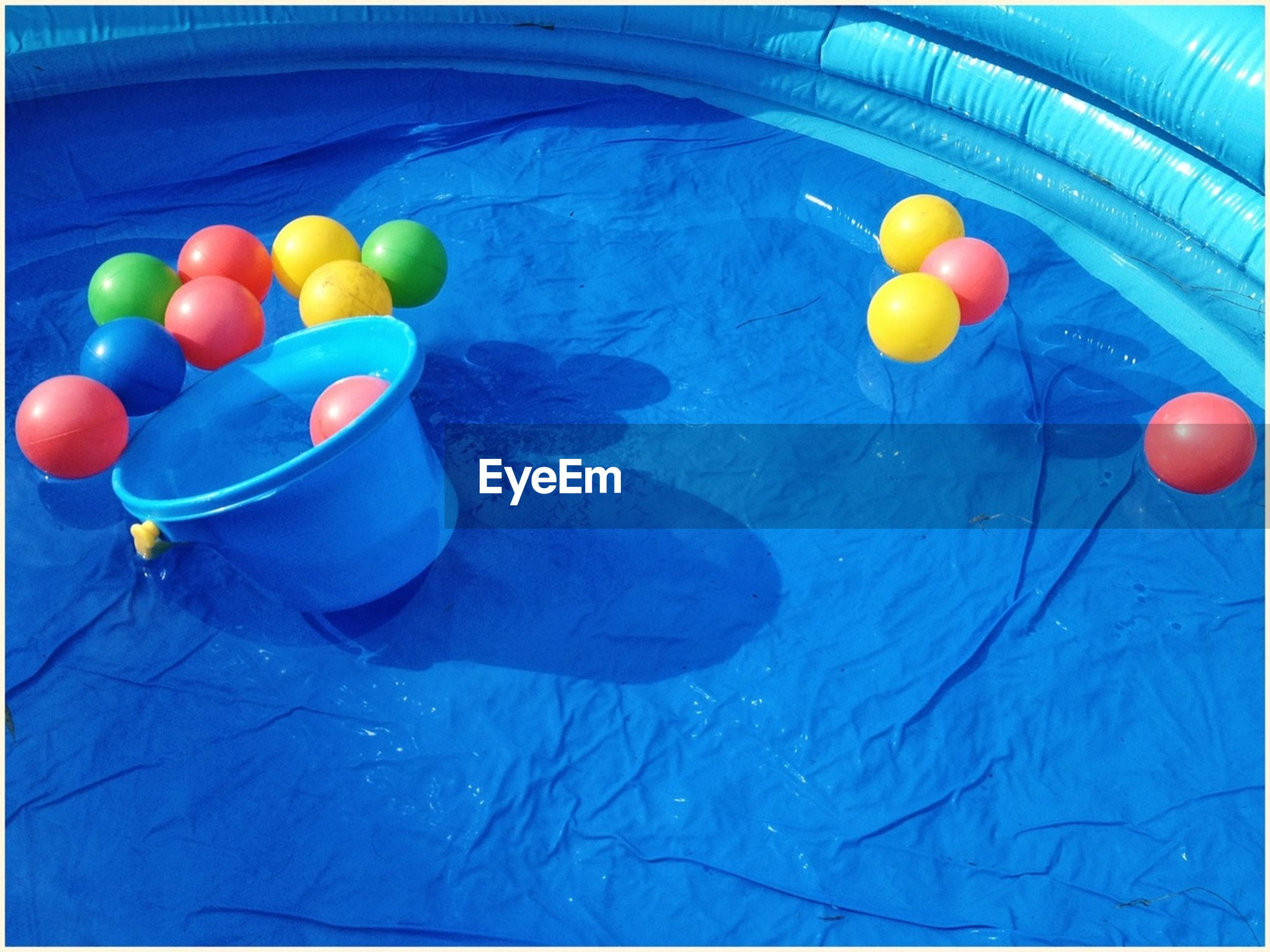 High angle view of balls and bucket in wading pool