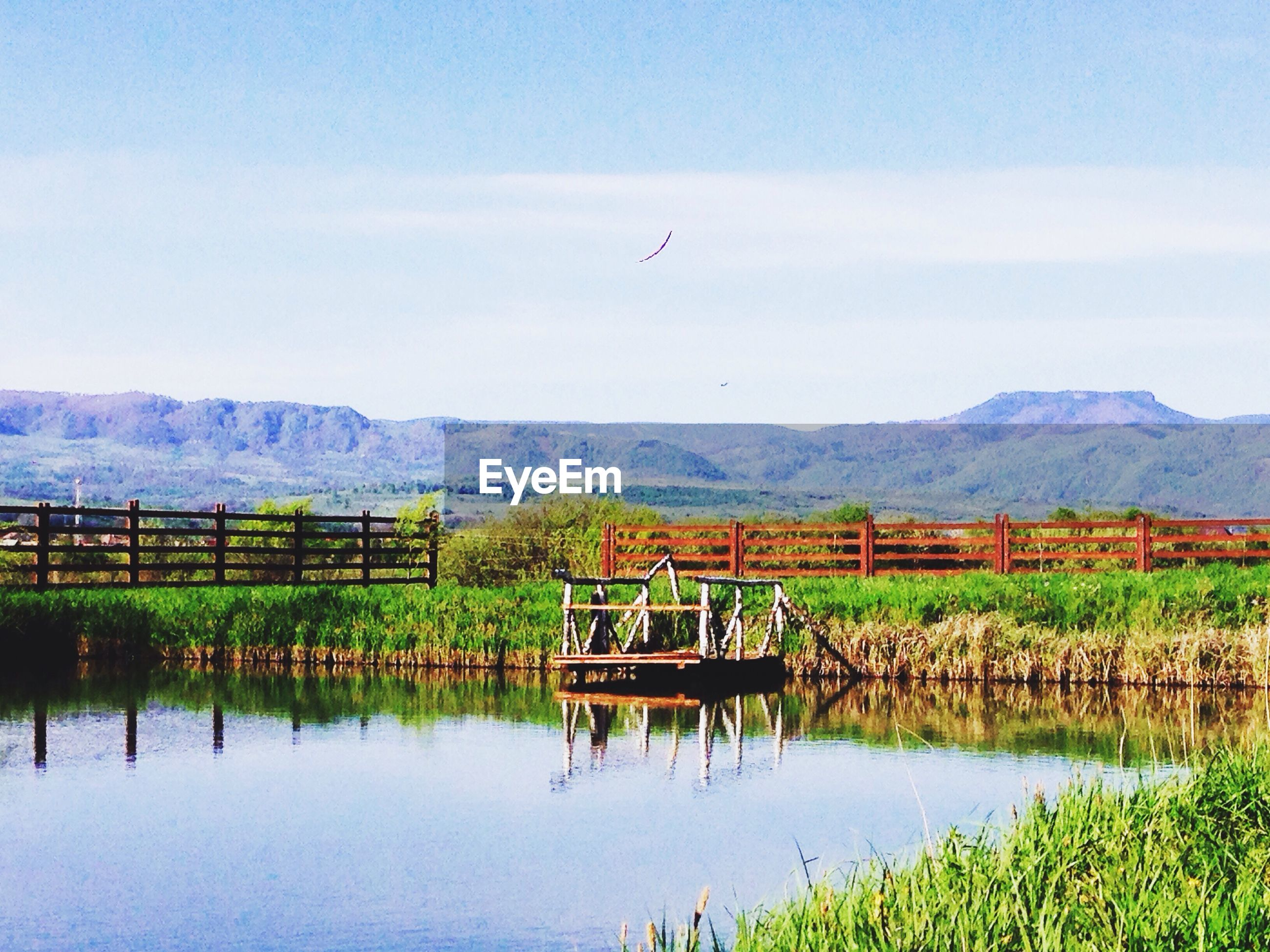 mountain, lake, tranquil scene, tranquility, water, scenics, landscape, mountain range, sky, transportation, nature, flying, beauty in nature, grass, mode of transport, day, non-urban scene, outdoors, bird, built structure