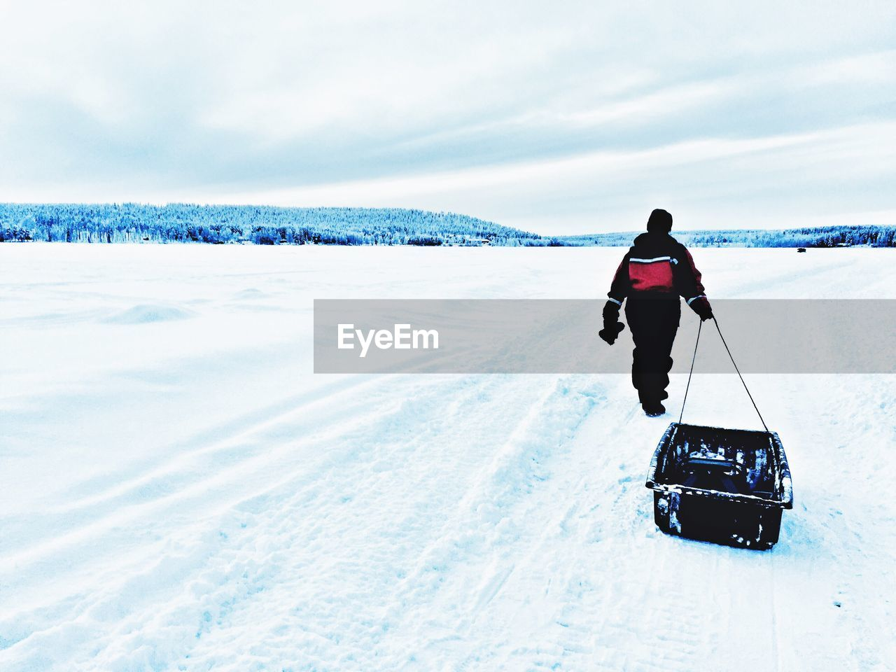 Full Length Rear View Of Man Walking With Container On Snow Covered Field Against Sky