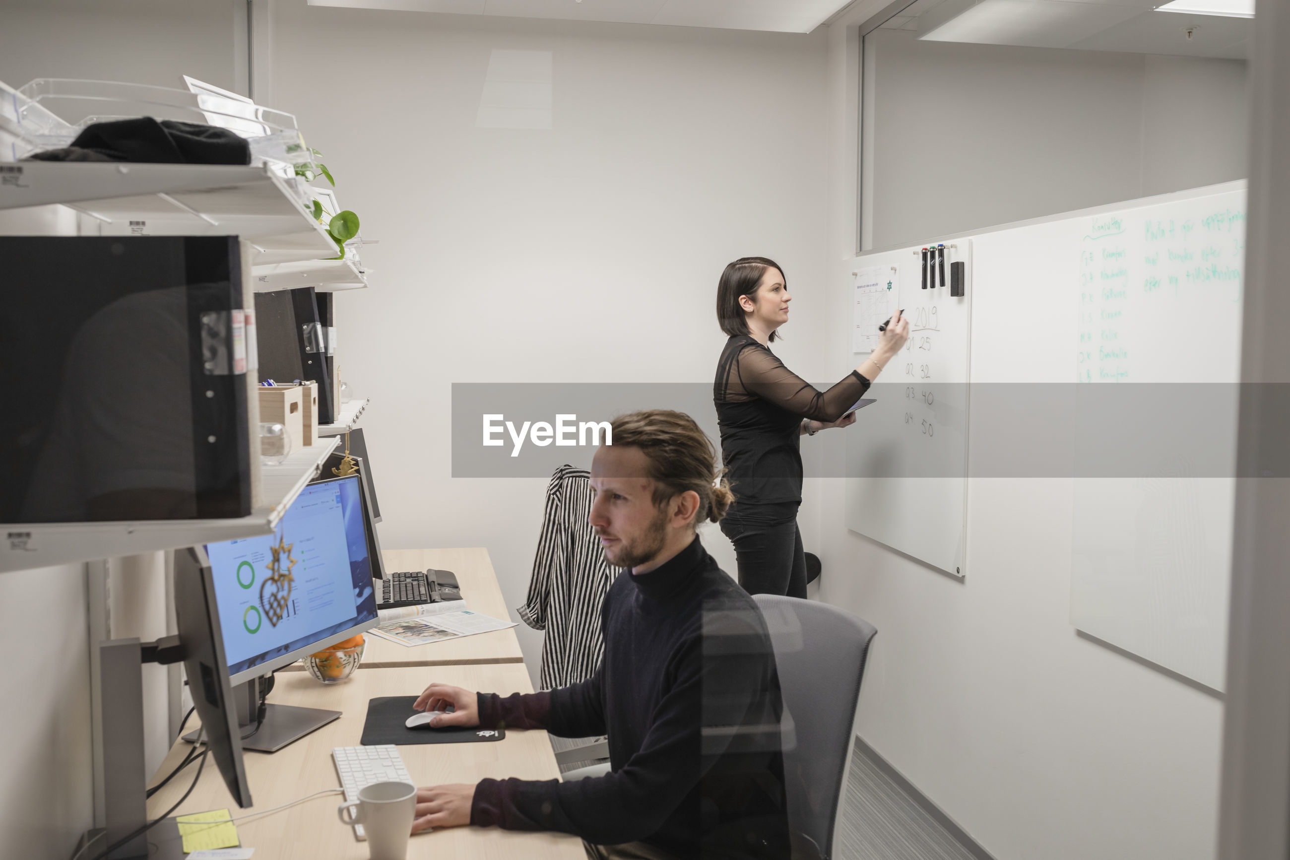 YOUNG COUPLE WORKING ON TABLE IN OFFICE