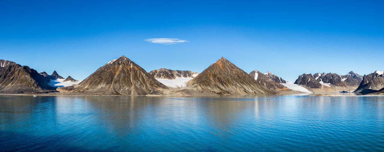 water, scenics - nature, sky, beauty in nature, blue, mountain, tranquil scene, tranquility, waterfront, nature, idyllic, non-urban scene, mountain range, day, no people, sea, remote, rock, outdoors, formation, mountain peak