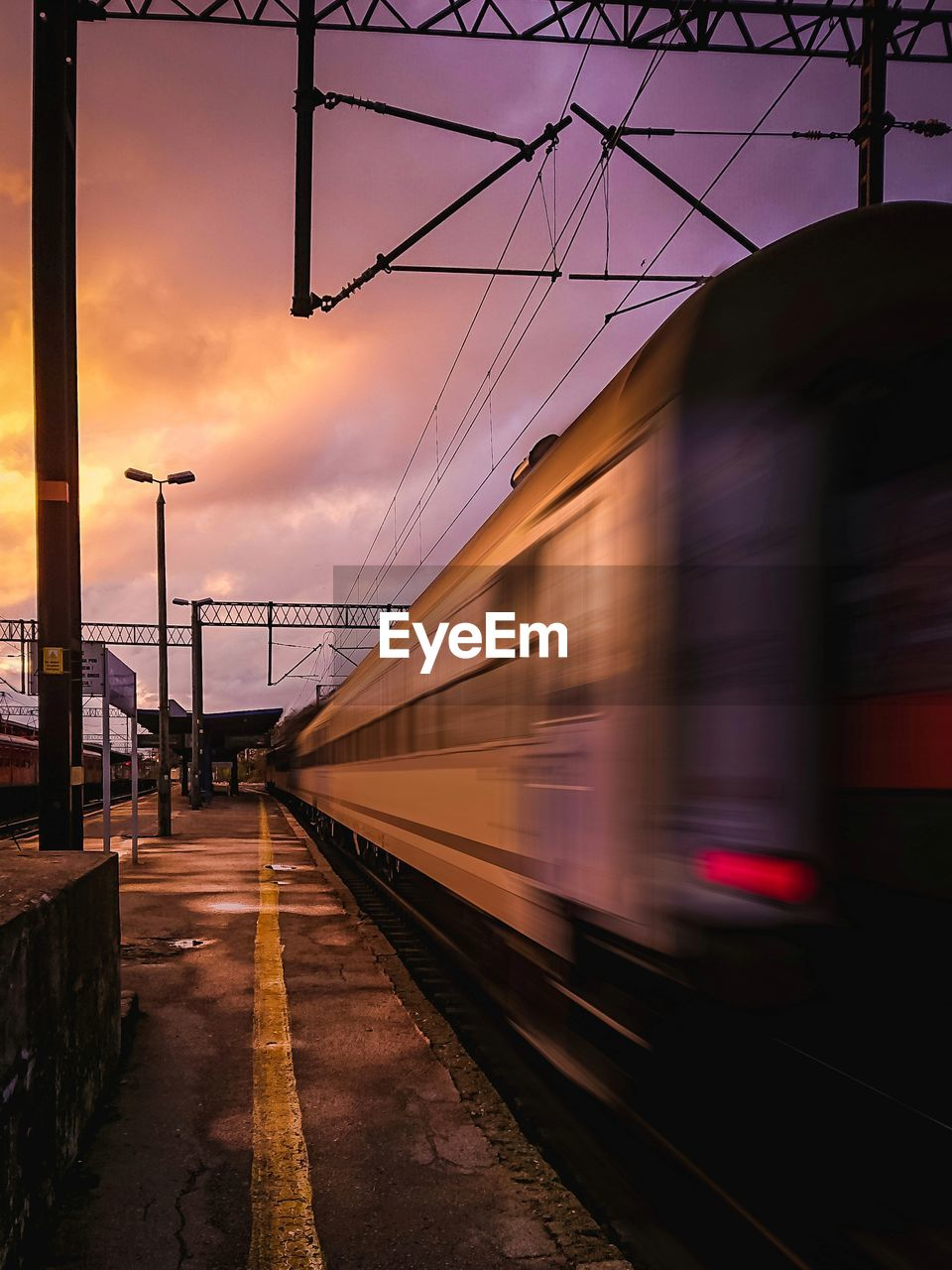 Blurred Motion Of Train At Railroad Station Against Sky During Sunset
