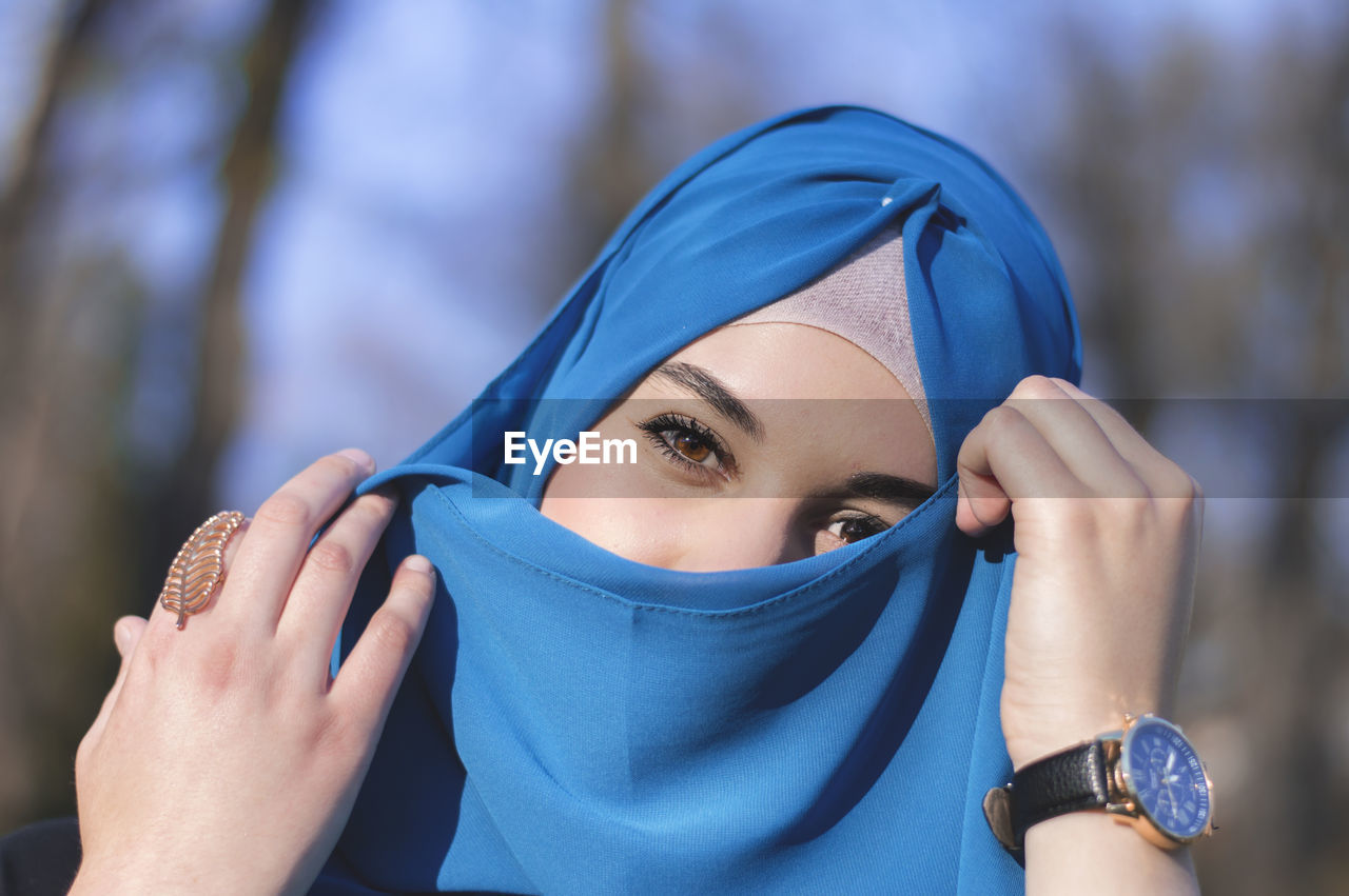 real people, hood - clothing, headshot, one person, focus on foreground, front view, lifestyles, blue, outdoors, leisure activity, close-up, young women, day, young adult